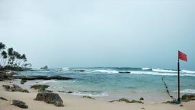 Sikt på havet och den sandiga stranden i Sri Lanka under storm Röd flagga som markerar det farliga stället för att simma Arkivfoto