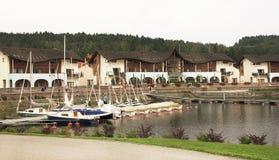 Sikt på hotell av Lipno nära sjön med yachter Royaltyfri Foto