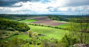 Sikt på landskap med grönt gräs, kullar och träd, molnig himmel royaltyfri fotografi