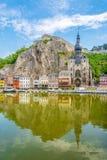 Sikt på reflexionen av hus och kyrkan av vår dam Assumption i Dinant - Belgien Royaltyfri Foto