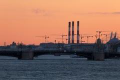 Sikt på slottbron i strålarna av solnedgången mellan slottfyrkanten och den Vasilievsky ön i St Petersburg arkivbild
