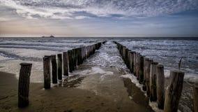Sikt på träpir under soligt väder med moln på stranden i Vlissingen, Zeeland, Holland, Nederländerna Royaltyfri Bild