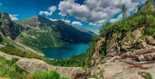 Sikt på turkosfärgsjön mellan höga och steniga berg royaltyfri fotografi