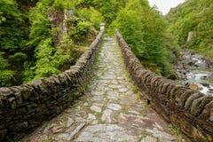 Sikt på vägen på det Ponte Romano Intragna Bridge nederlaget i vaen arkivfoto