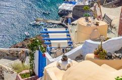 Sikt på fartyg och kaféer av Santorini från klippan på den Oia staden Arkivfoton