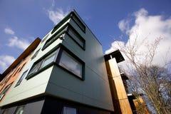 Sikt som ser upp på en modern hyreshus med a med en CCTV-kamera arkivfoton