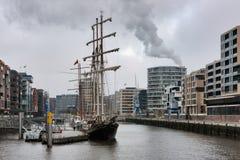 Sikt som ska härbärgeras med förtöjde segelbåtar i modernt område för `-HafenCity ` av Hamburg Arkivbild