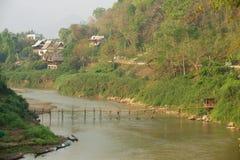 Sikt till bostadsområdet av staden över floden med en bro i Luang Prabang, Laos Arkivbilder