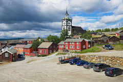Sikt till de traditionella trähusen och tornet för kyrklig klocka av kopparminstaden av Roros i Roros, Norge arkivbilder