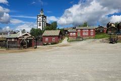 Sikt till de traditionella trähusen och tornet för kyrklig klocka av kopparminstaden av Roros i Roros, Norge royaltyfri bild