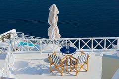 Sikt till de två chaisna med en havssikt på ett hotelltak i Oia, Grekland Royaltyfri Fotografi
