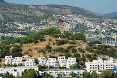 Sikt till de vita bostadsområdebyggnaderna med den turkiska nationsflaggan på en kulle i Bodrum, Turkiet Arkivbilder