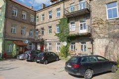 Sikt till den gamla bostads- byggnaden med inskränkt utrymme för bilparkering i Vilnius, Litauen Royaltyfri Bild