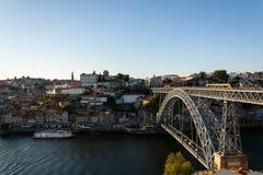 Sikt till den gamla staden av Porto med Det Luis bro och färgrika byggnader Varmt guld- ljus royaltyfria bilder