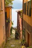Sikt till den italienska sjön Como från en av de smala gatorna royaltyfri foto