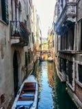 Sikt till den lilla kanalen med gamla byggnader och fartyget på Venedig Arkivbild