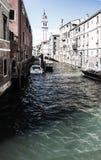 Sikt till den lilla kanalen med gamla byggnader och fartyget på Venedig Arkivfoton