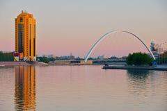 Sikt till den stadsbyggnaderna och bron över den Ishim floden på skymning i Astana, Kasakhstan Royaltyfri Foto