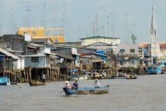 Sikt till det styltahusen och folket som korsar floden med fartyget i Cai Be, Vietnam Arkivfoto