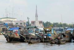 Sikt till fartygen som svävar på vatten med kyrkan på bakgrunden i Cai Be, Vietnam Royaltyfri Bild