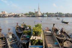Sikt till fartygen som svävar på vatten med kyrkan på bakgrunden i Cai Be, Vietnam Royaltyfri Fotografi