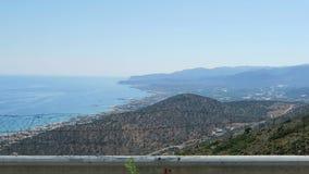Sikt till fjärden av Malia Crete Greece diriving tillsammans med ett vägdrev i bergen arkivfilmer