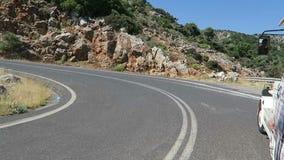 Sikt till fjärden av Malia Crete Greece körning tillsammans med ett vägdrev i bergen stock video