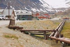 Sikt till gatan av Longyearbyen med uppvärmningrör på förgrunden i Longyearbyen, Norge Fotografering för Bildbyråer
