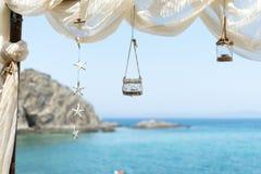 Sikt till havet från en strandstång, med markisen, lyktan och stjärnor Arkivfoto