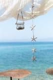 Sikt till havet från en strandstång, med markisen, lyktan och stjärnor Arkivbild