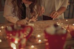 Sikt till kvinnas och barns händer på tabellen som pudras av mjöl arkivfoton