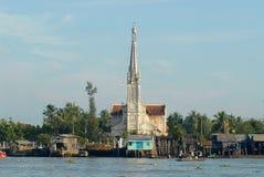 Sikt till kyrklig byggnads- och styltahusen i Cai Be, Vietnam Royaltyfri Bild