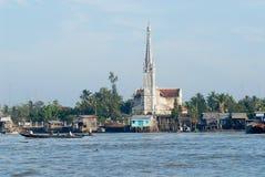 Sikt till kyrklig byggnads- och styltahusen i Cai Be, Vietnam Arkivbild