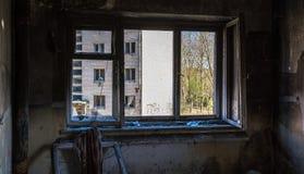 Sikt till och med det brutna fönstret i övergett hus royaltyfri foto