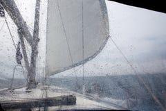 Sikt till och med exponeringsglaset med regndroppar som seglar yachten Royaltyfri Fotografi