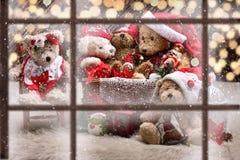 Sikt till och med fönster till familjen för nallebjörn som firar jul Royaltyfria Bilder