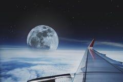 Sikt till och med flygplanfönster resa med nivån med härlig flyg- himmel med fullmånen och stjärnor på natten Arkivfoto