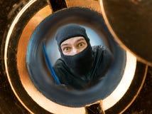 Sikt till och med kikhål Rånare eller inbrottstjuv som maskeras med balaclavaen bak dörr fotografering för bildbyråer