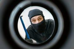 Sikt till och med kikhål Tjuven eller inbrottstjuven som maskeras med balaclavaen, är bak dörren royaltyfri foto