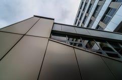 Sikt till och med modern hög resningskyskrapa uppåt till blå himmel med vita moln - abstrakt arkitekturdetaljbakgrund Arkivfoto