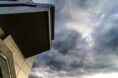 Sikt till och med modern hög resningskyskrapa uppåt till blå himmel med vita moln - abstrakt arkitekturdetaljbakgrund Fotografering för Bildbyråer