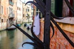 Sikt till och med stängerna på en Venetian kanal från bron Sommar Arkivbild