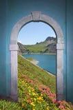 Sikt till och med välvd dörr; alpin sjö och berg Royaltyfri Bild