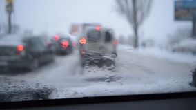 Sikt till och med vindrutan på defocused plats på den snöig stadsvägen stock video
