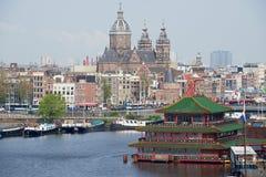 Sikt till staden av Amsterdam med kanalen, historiska byggnader och basilikan av St Nicholas i Amsterdam, Nederländerna Arkivbilder