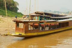 Sikt till traditionella långa fartyg som binds på den sandiga banken av Mekong River i torr säsong i Luang Prabang, Laos Arkivbilder