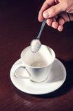 Sikta socker i koppen Arkivfoto