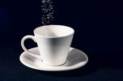 Sikta socker i koppen Arkivbild