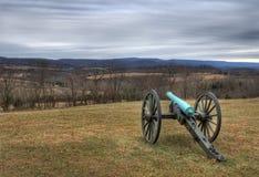 siktar kanonen som borgerliga berg in mot kriger Royaltyfri Bild