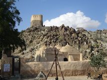 Sikten av den äldsta moskén och en portugisisk fortklocka står högt på kullen i Fujairah i Förenadeen Arabemiraten Arkivbilder